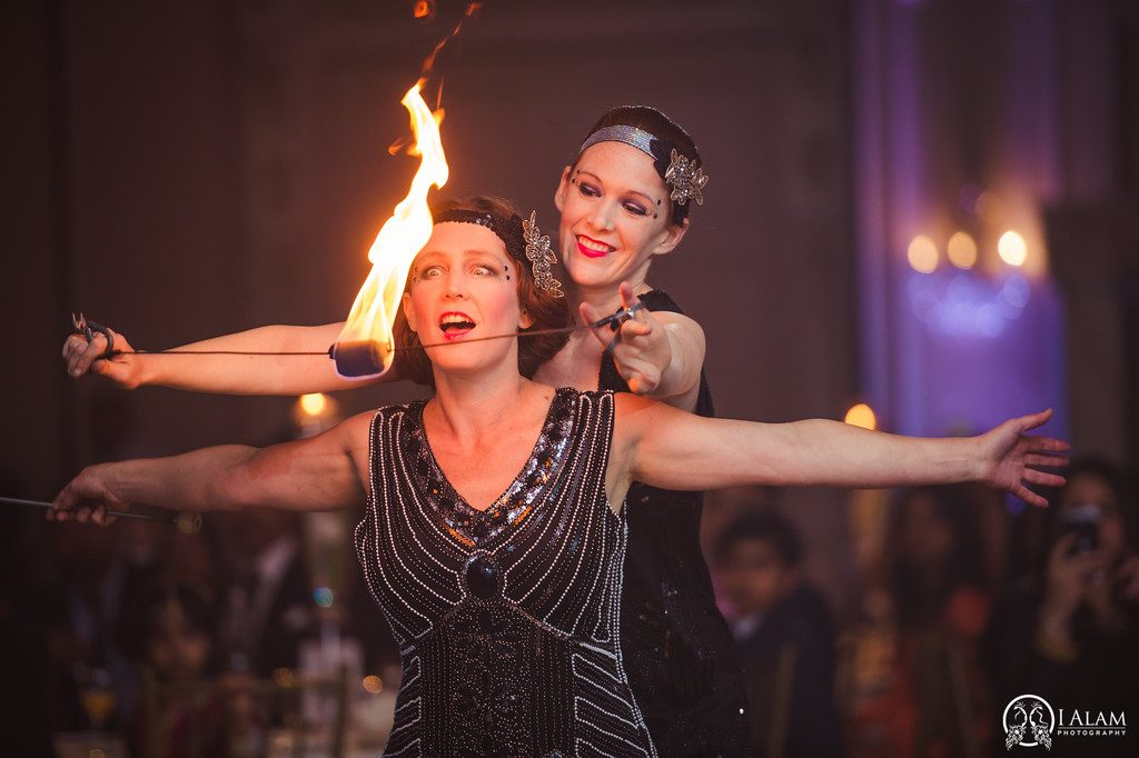 2 women in 1920s costumes with fire orb in front of their astonished faces